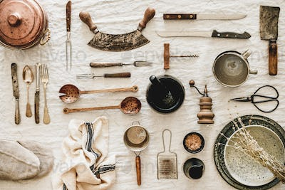 Kitchen utensils and tablewear over linen tablecloth, top view