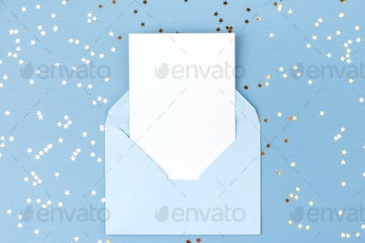 Empty Card in Blue Envelope on Blue Background Decorated with Confetti.