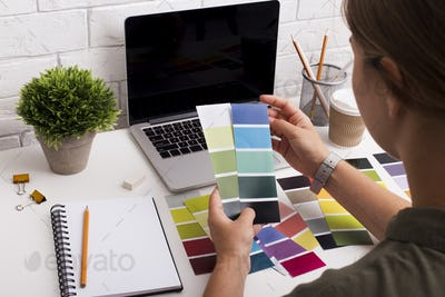 Young girl designer picking up colors for clients on workplace
