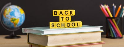 Back to school text with books and stationery over chalkboard