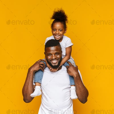 Millennial african father riding his little daughter on shoulders