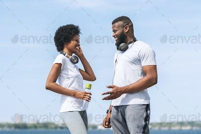 Man And Woman Talking After Morning Jog Near River