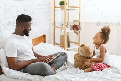 African man sitting on bed with daughter, looking at each other