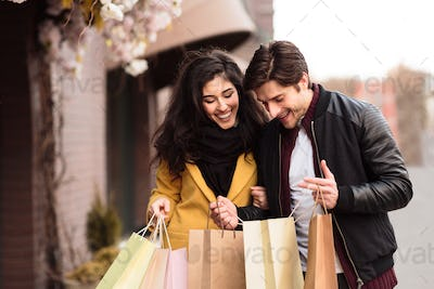 Happy couple looking into shopping bags, examining purchases