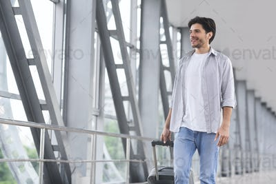 Millennial tourist with luggage in airport, enjoying future trip