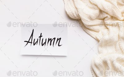 Creative autumn background with white wool scarf