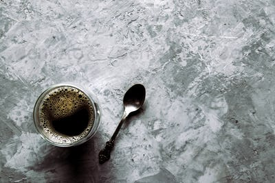 large transparent glass filled with of aromatic Turkish coffee photographed on the gray background