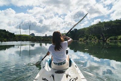 Young woman tourist paddling the kayak at klong root in Krabi, Thailand