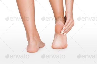 Young woman touching her painful sole, isolated on white