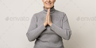 Aged woman with clasped hands, pleading or appealing for something.