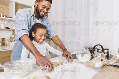 Happy african father and daughter rolling dough together
