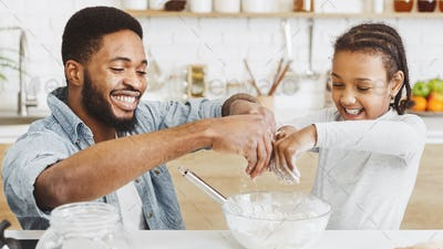 Happy dad and daughter adding flour into dough bowl