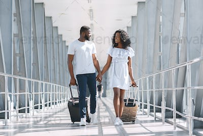 Black couple in love going on flight departure with suitcases