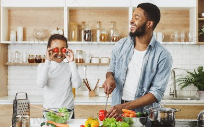Positive dad and daughter having fun on kitchen