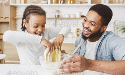 Excited little black girl playing with pastry dough