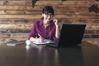 Smiling businesswoman listening to music at work