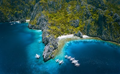 El Nido, Palawan, Philippines. Aerial view of Miniloc Island with diving boats above coral reef