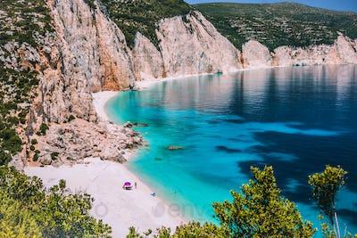 Amazing Fteri beach lagoon, Kefalonia, Greece. Tourists under umbrella chill relax near clear blue