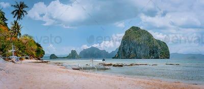 Panoramic view of El Nido coastline with traditional filippino boats on beach and Pinagbuyutan