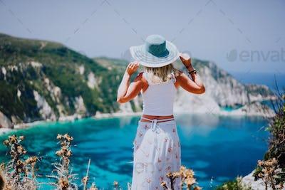 Young woman on Petani beach Kefalonia, holding blue sunhat enjoying picturesque panorama of emerald
