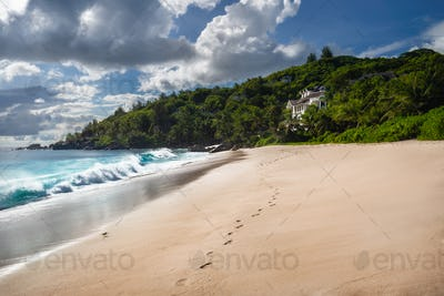 Exotic tropical beach Anse Takamaka on Seychelles islands, Mahe. Scenic view with impressive clouds