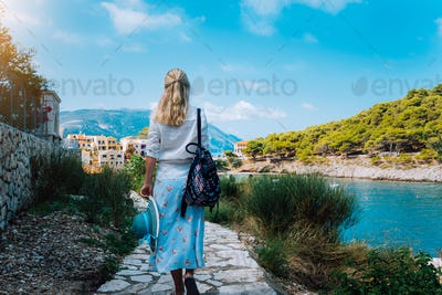 Attractive fashion woman on summer vacation on Kefalonia Island. Beautiful tanned woman with straw
