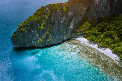 Aerial drone view of tropical beach with banca boats on Entalula Island. Karst limestone rocky