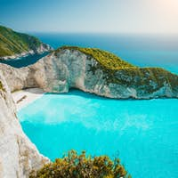 Navagio beach or Shipwreck bay panoramic. Turquoise sea water and white beach between huge cliffs