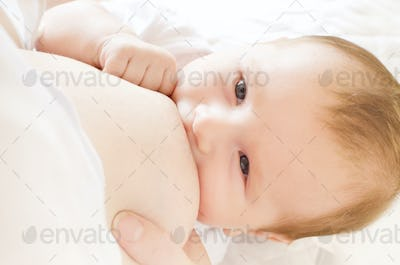 Young woman breastfeeding her little baby boy closeup