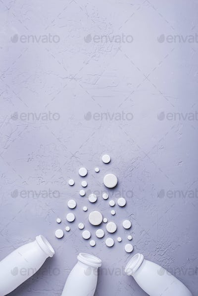 Different pills and tablets on grey background