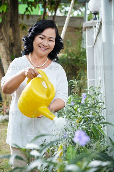 Senior woman watering the plants