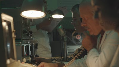Scientists working in a vintage control room