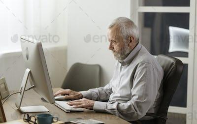 Senior man using his computer at home