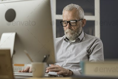 Senior man connecting with his computer at home