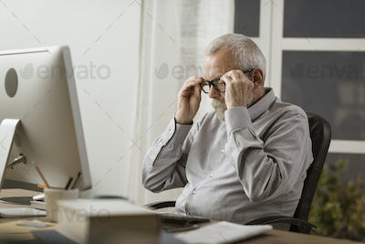 Senior man adjusting his glasses and working with his computer