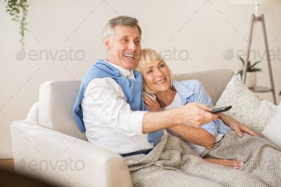 Relaxed senior couple watching television at home
