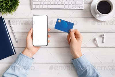 Woman using smartphone and credit card for online shopping