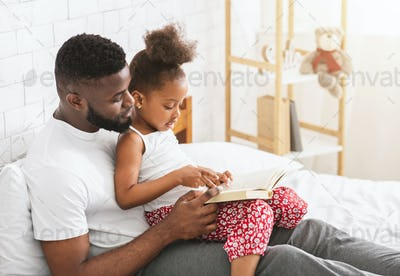 African american father teaching his little daughter how to read