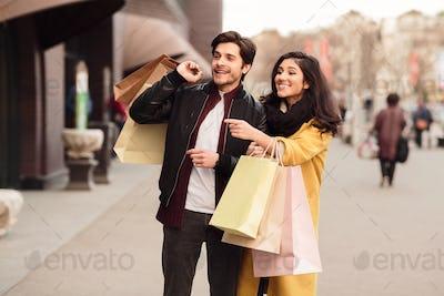 Woman showing fashion store, walking with husband