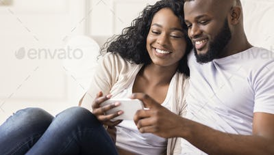 Happy african couple watching funny videos on smartphone at home