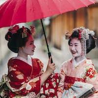 Maiko geishas walking on a street of Gion