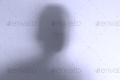 Defocused scary ghost face behind a white glass background
