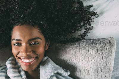 Beautiful black woman with curly hair smiling and lying on bed looking at the camera