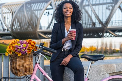 Business black woman with vintage bicycle drinking coffe
