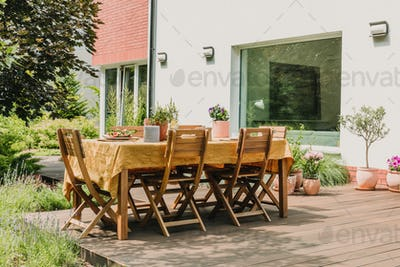Dining table covered with orange tablecloth standing on wooden terrace in green garden