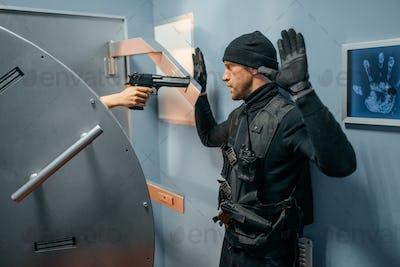 Robber standing at vault door with his hands up