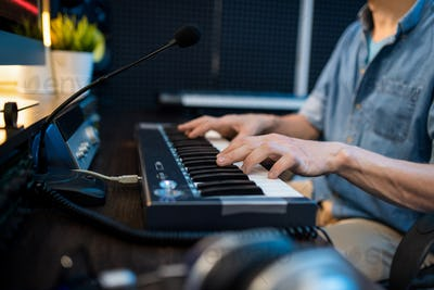 Young male musician touching keys of piano keyboard while sitting by workplace