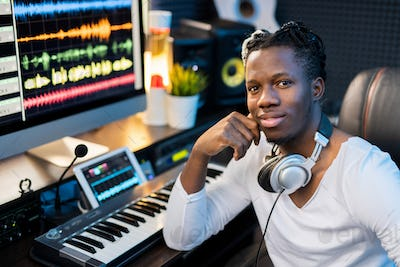Happy young smiling mixed-race man with headphones on neck sitting by workplace