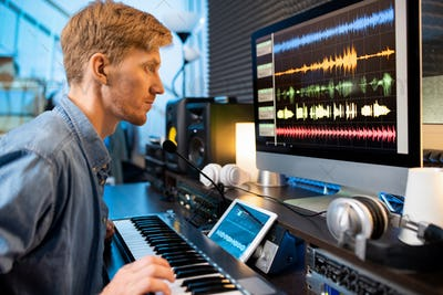 Serious man touching one of pianoboard keys while looking at sound waveforms