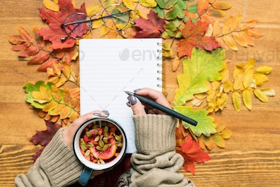 Overview of student hands holding hot herbal tea and pen over open copybook